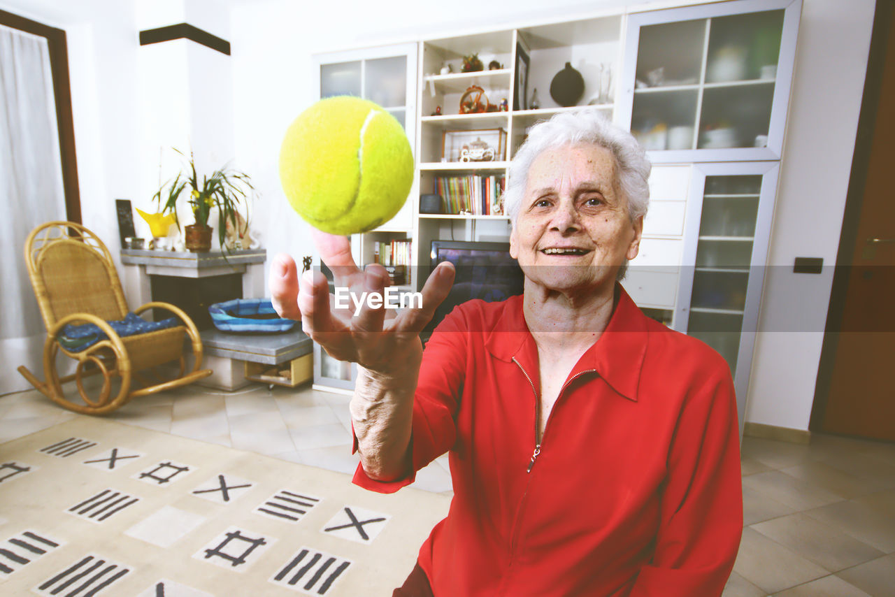 Portrait of happy senior woman catching ball at home