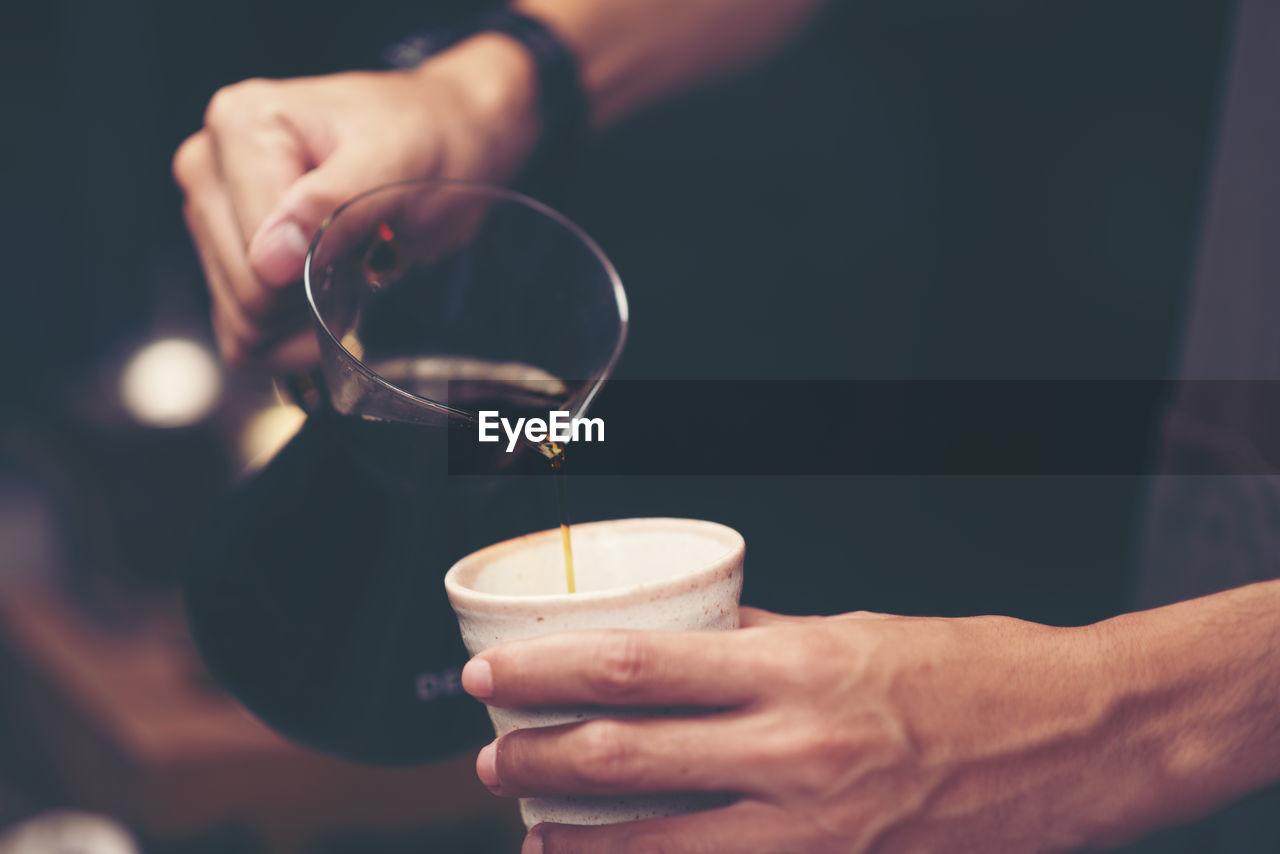 Cropped Image Of Man Pouring Black Coffee In Mug