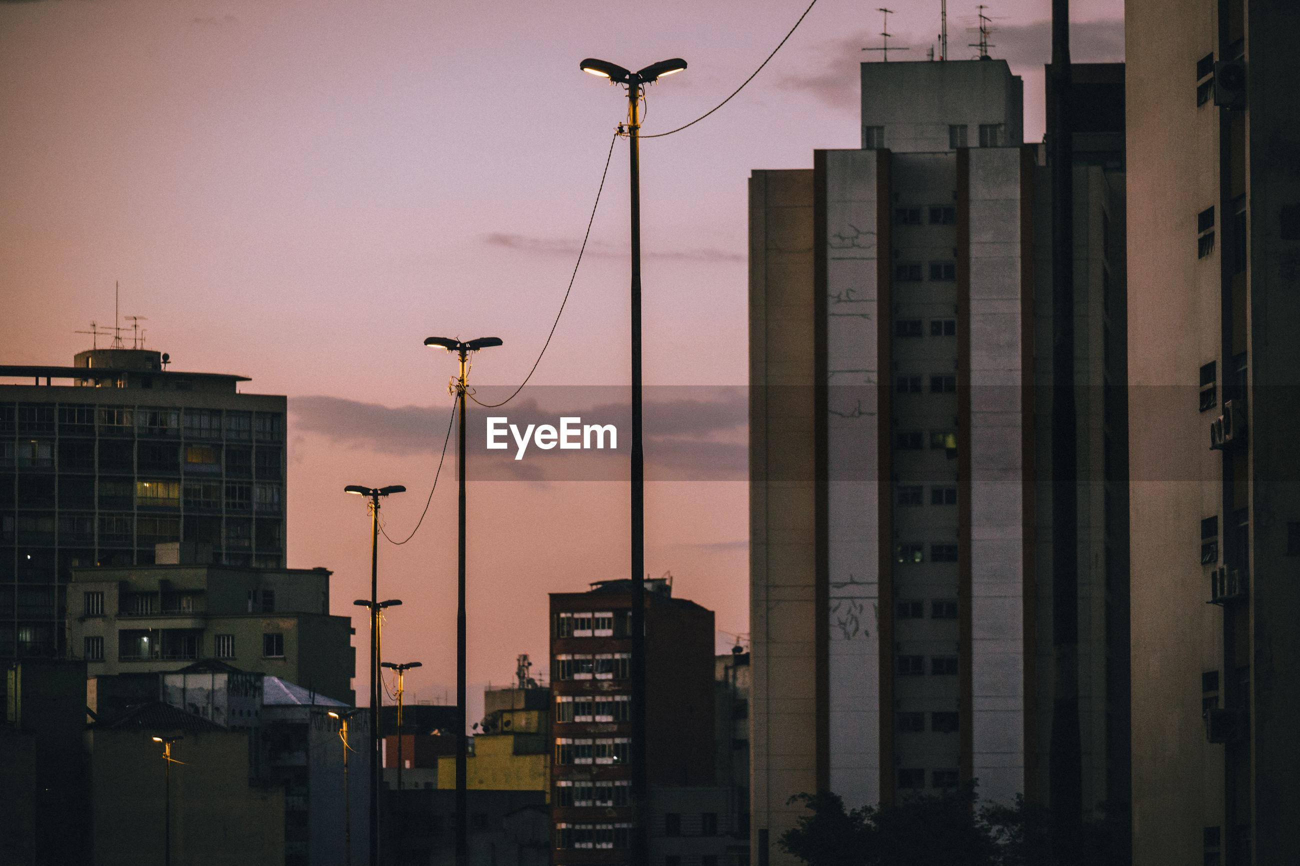 Illuminated city against sky at sunset