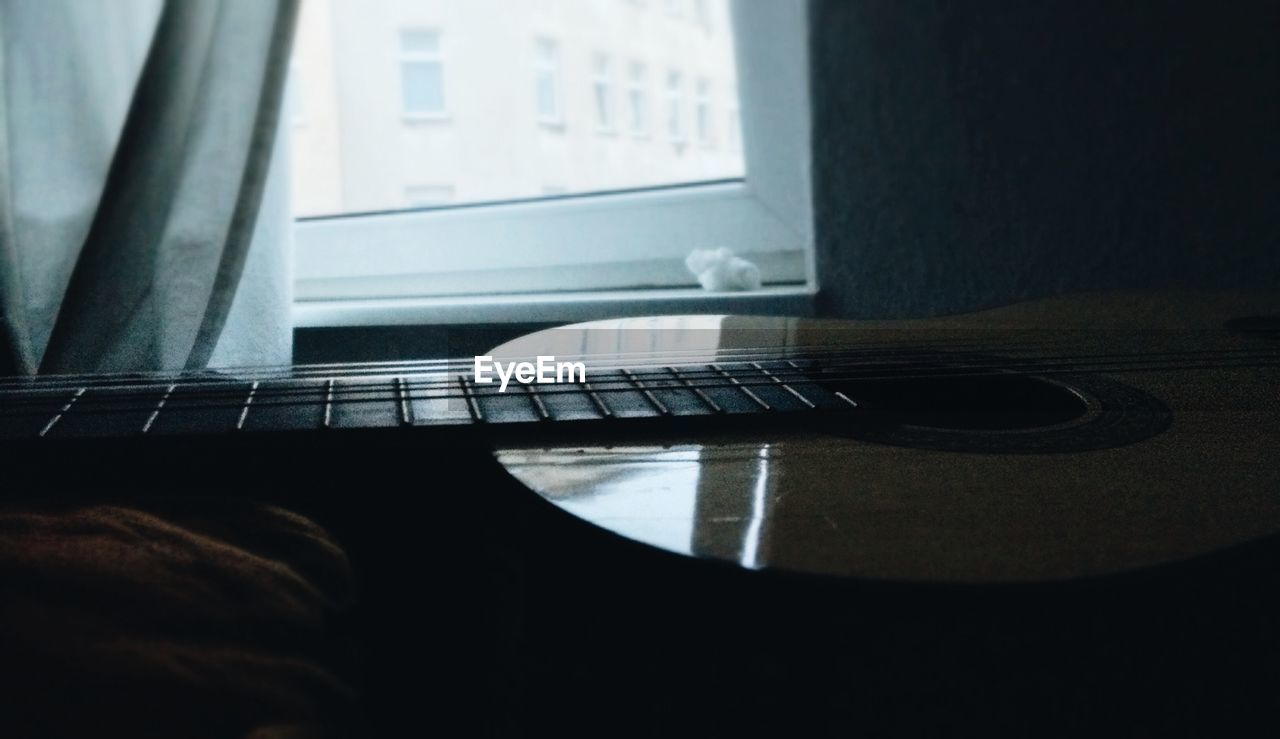Cropped image of guitar by window