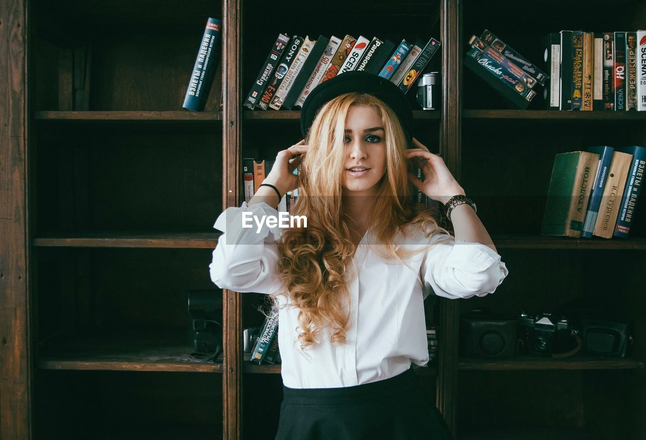 Portrait Of Beautiful Woman Standing Against Bookshelf In Library