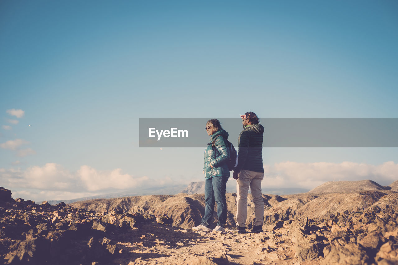 Couple Standing On Ground Against Blue Sky
