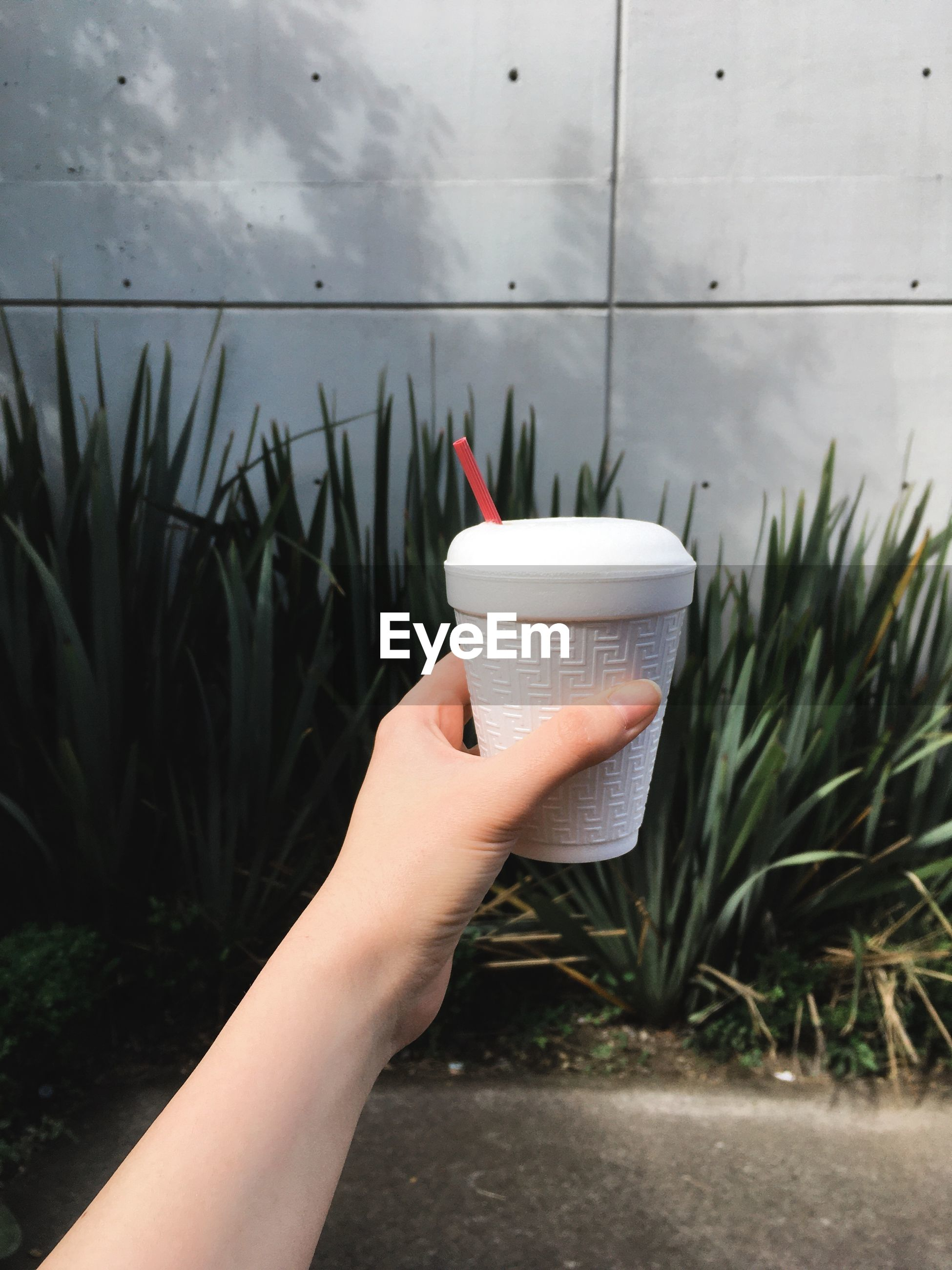 Cropped hand of person holding coffee cup against wall outdoors