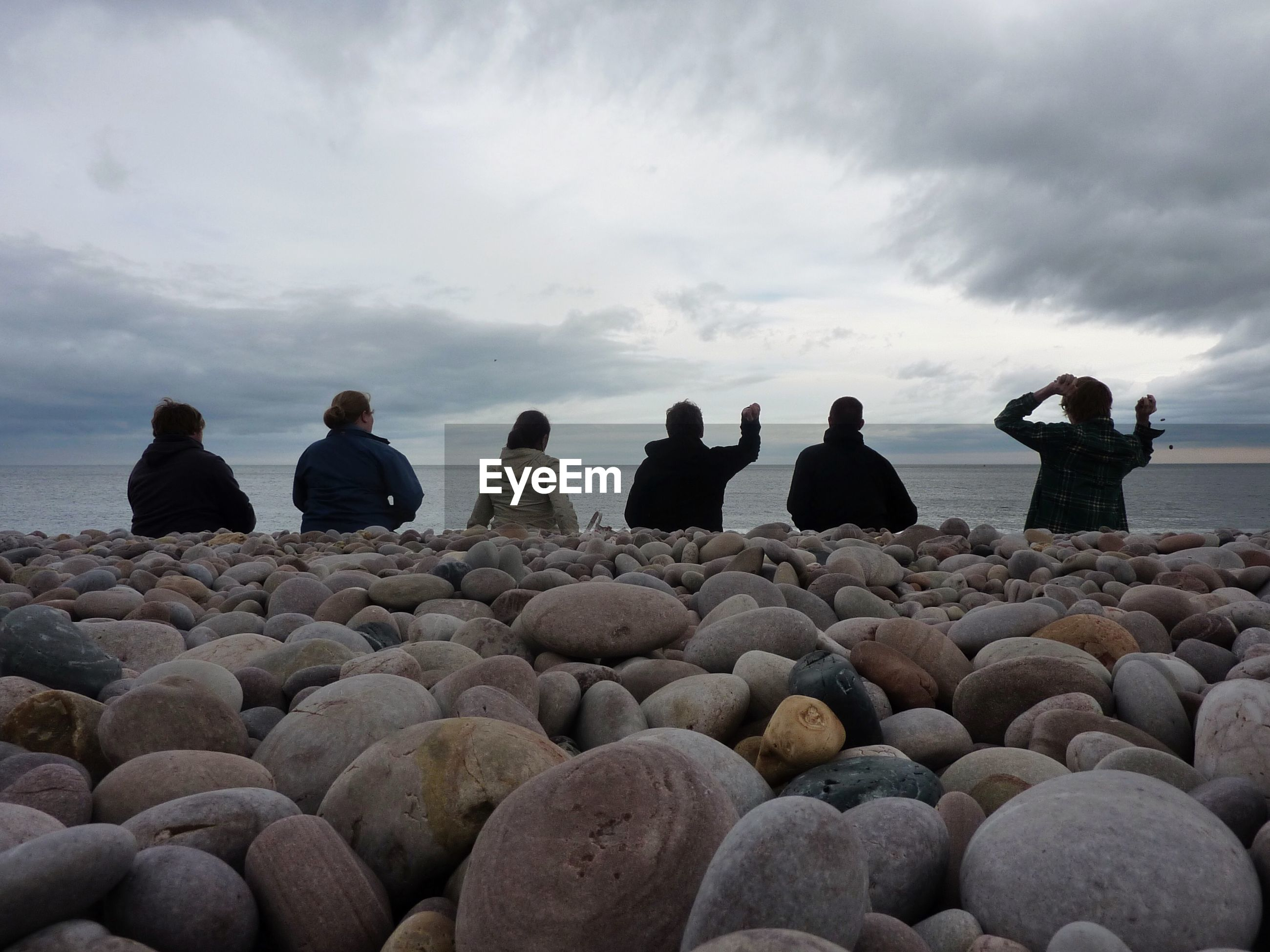 Rear view of friends standing at beach