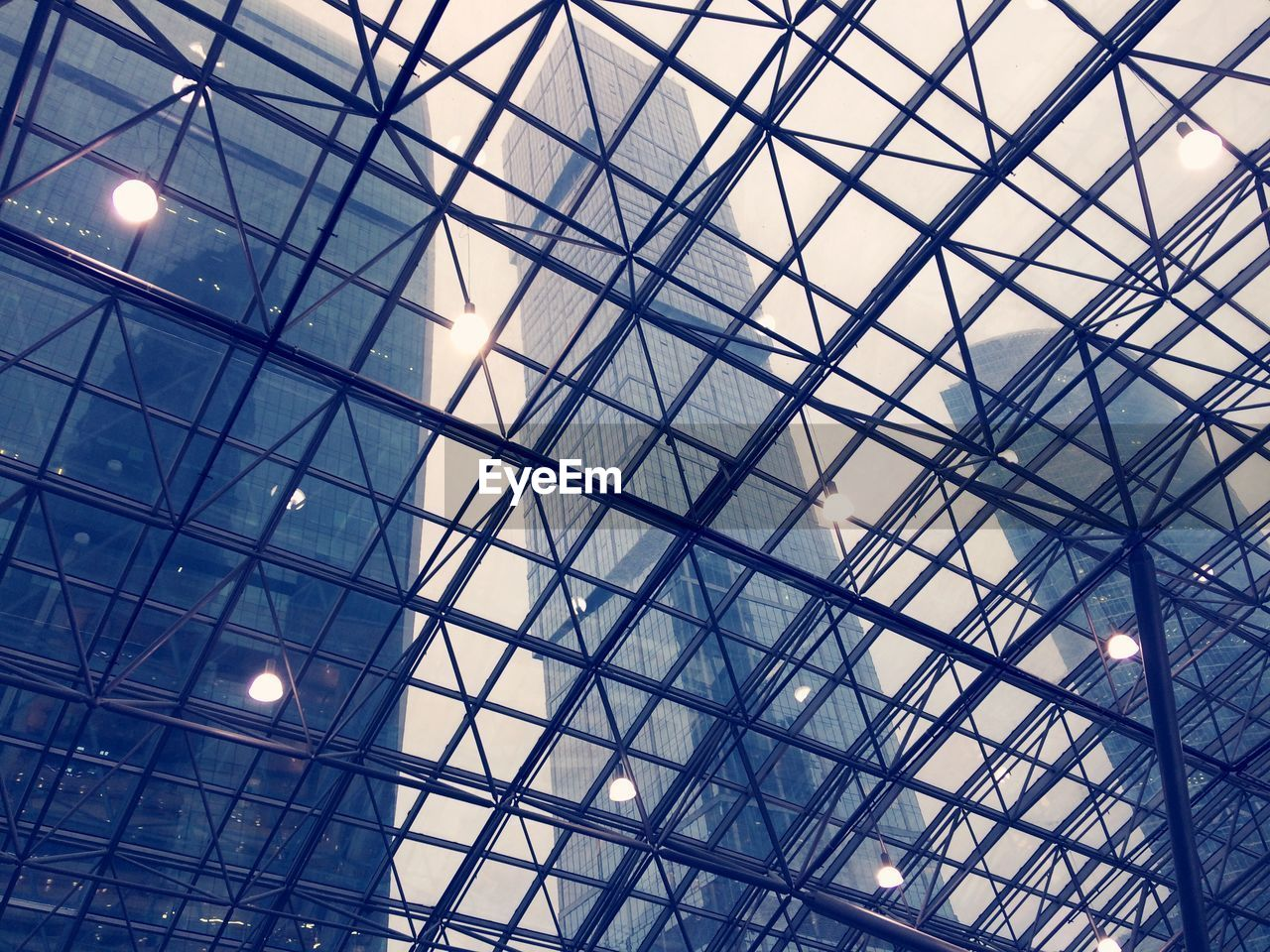 low angle view, architecture, built structure, full frame, no people, lighting equipment, ceiling, glass - material, indoors, modern, illuminated, backgrounds, pattern, transparent, geometric shape, sky, day, nature, sunlight, skylight, light