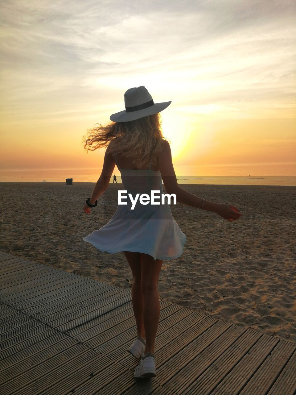 Rear view of woman walking on boardwalk at beach during sunset