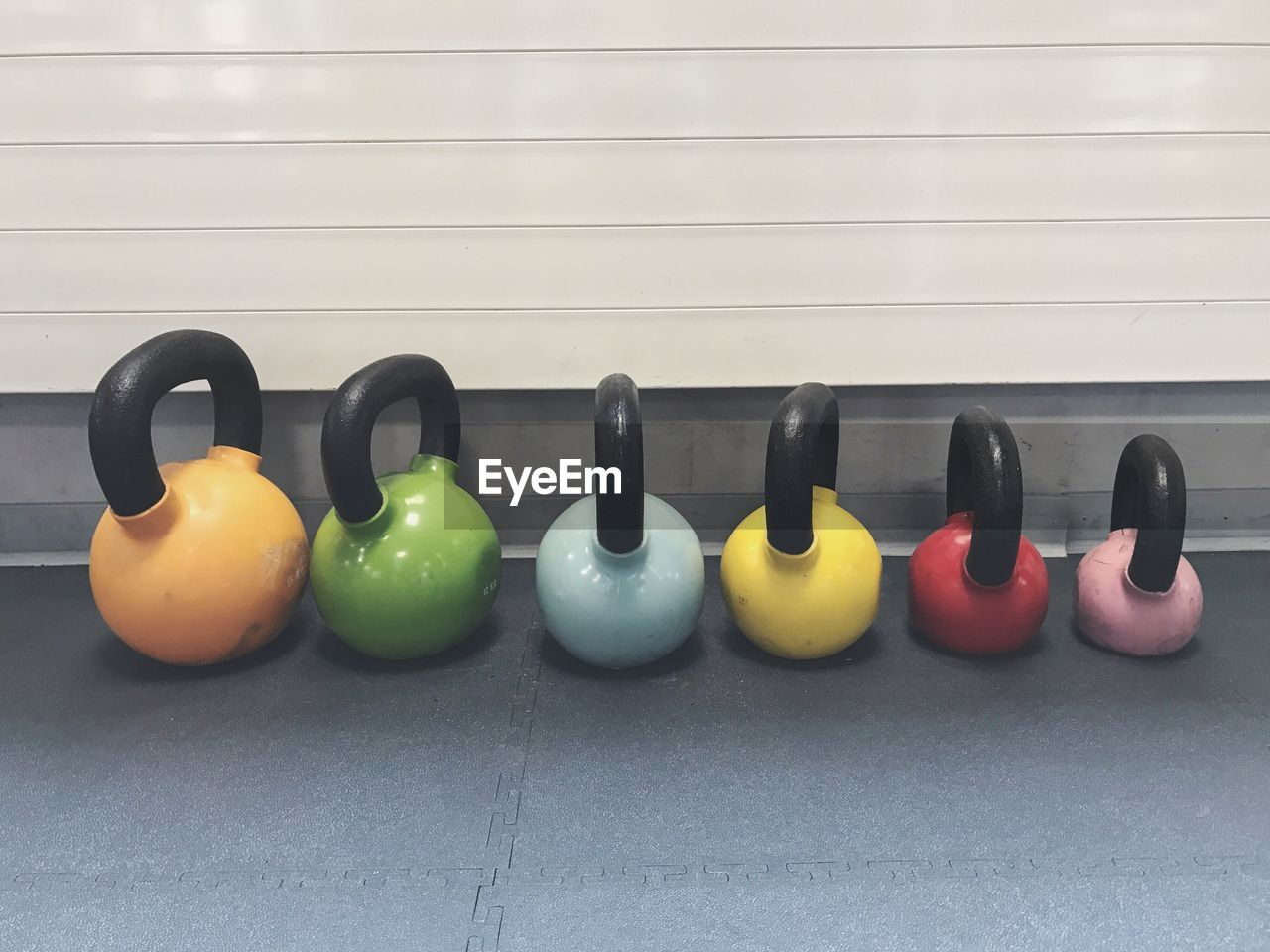 Multi Colored Kettlebells Arranged Side By Side In Gym