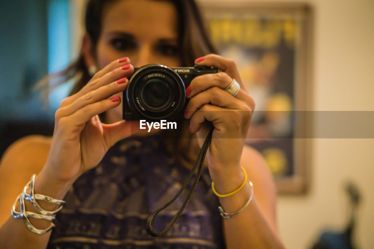Young woman photographing through camera at home