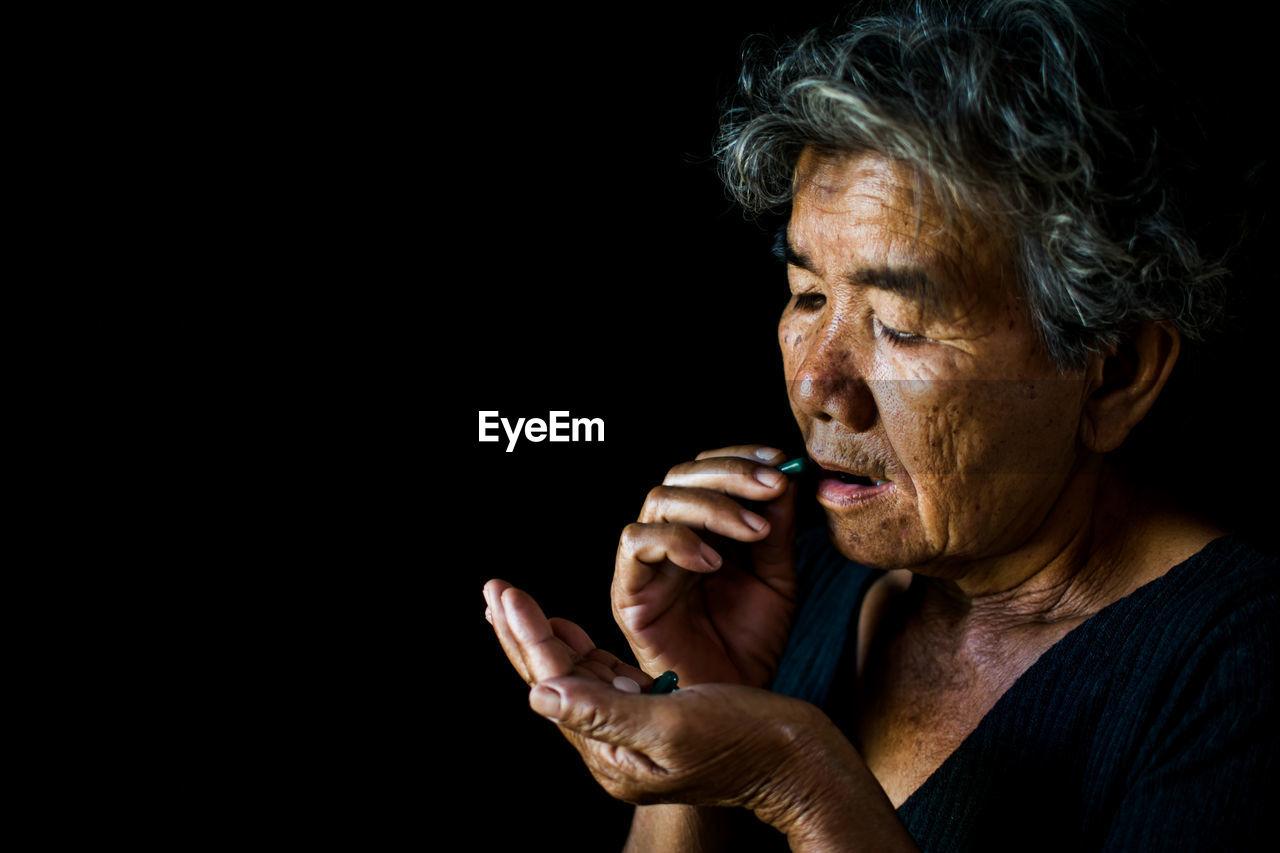 Close-up senior woman eating pills against black background