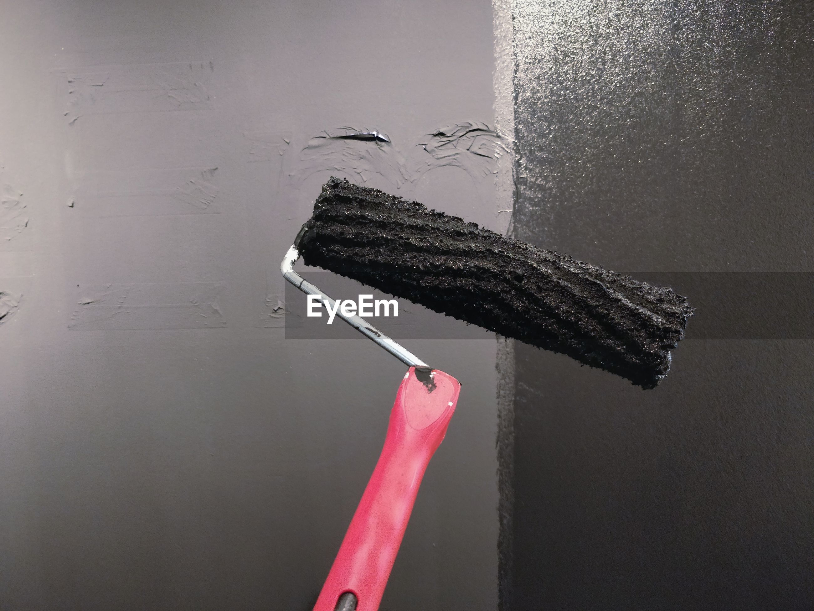 Close-up of paint roller against black wall