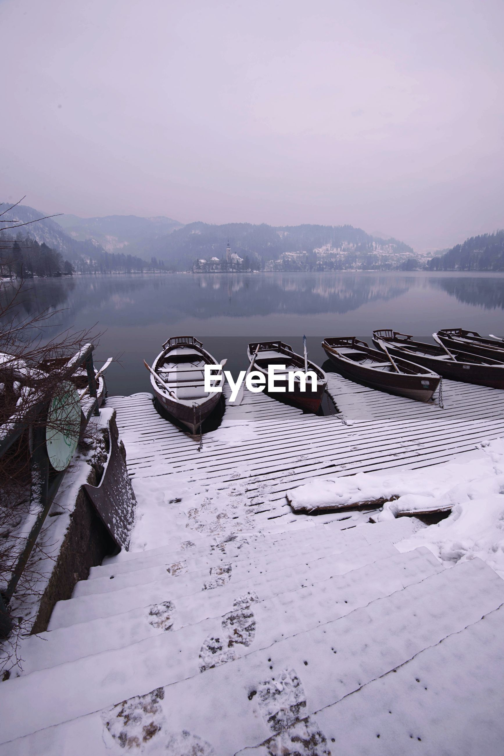 BOATS MOORED ON FROZEN LAKE AGAINST SKY