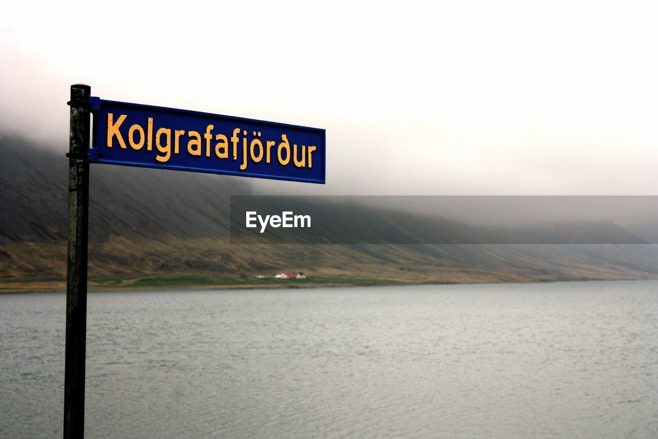 Close-Up Of Information Sign By River Against Sky During Foggy Weather