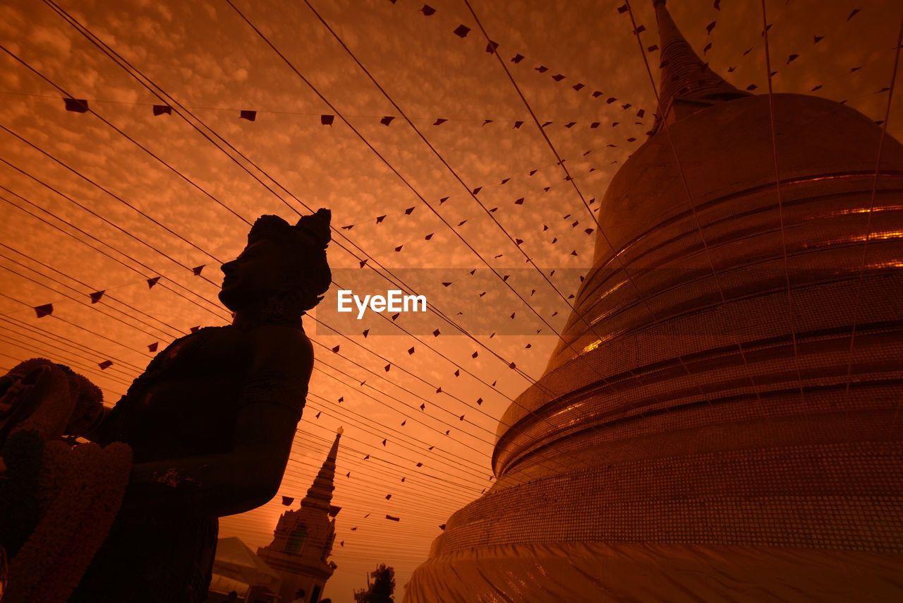 Low angle view of decorations and stature at temple against orange sky during sunset