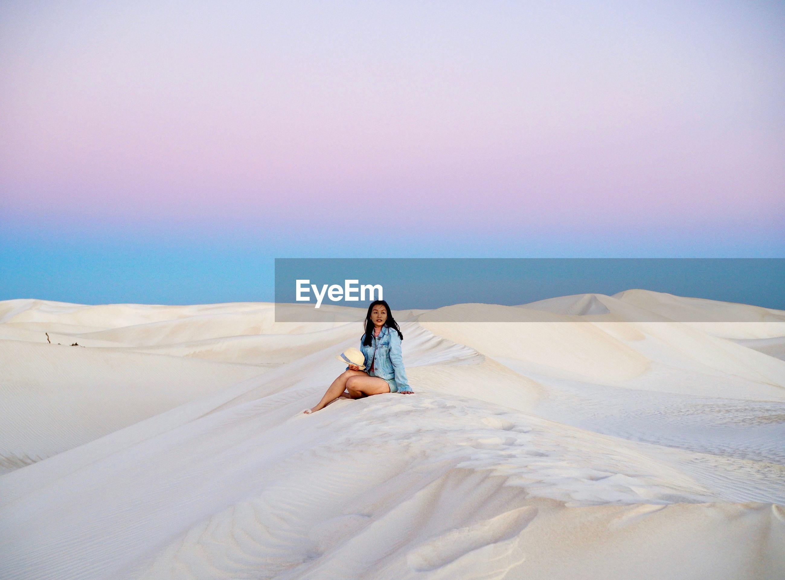 Full length of woman sitting on sand dune against sky during sunset