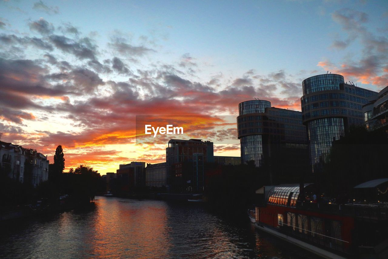 sky, architecture, building exterior, sunset, built structure, cloud - sky, city, water, building, nature, no people, waterfront, orange color, transportation, river, reflection, outdoors, office building exterior, cityscape, skyscraper