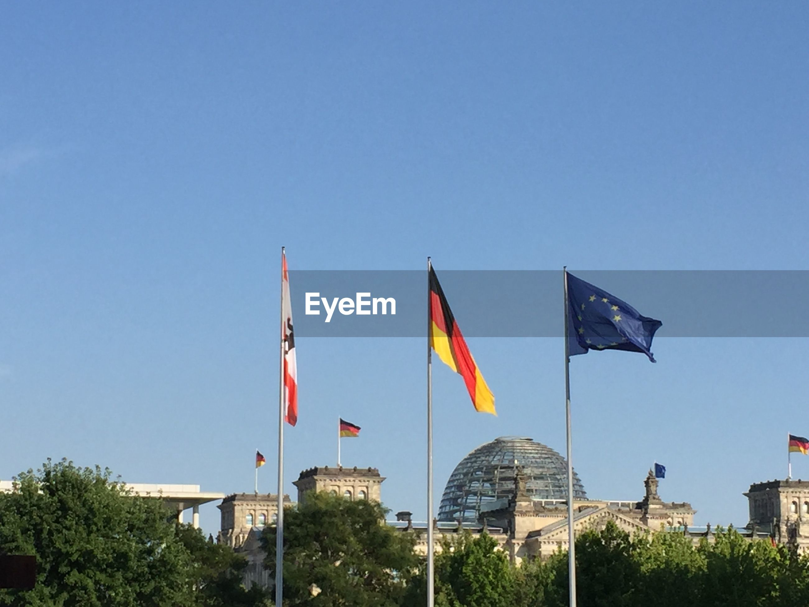 Low Angle View Of German Flag By The Reichstag Against Sky