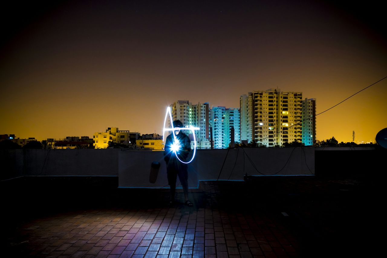Young man making light painting while standing on street against clear sky at night