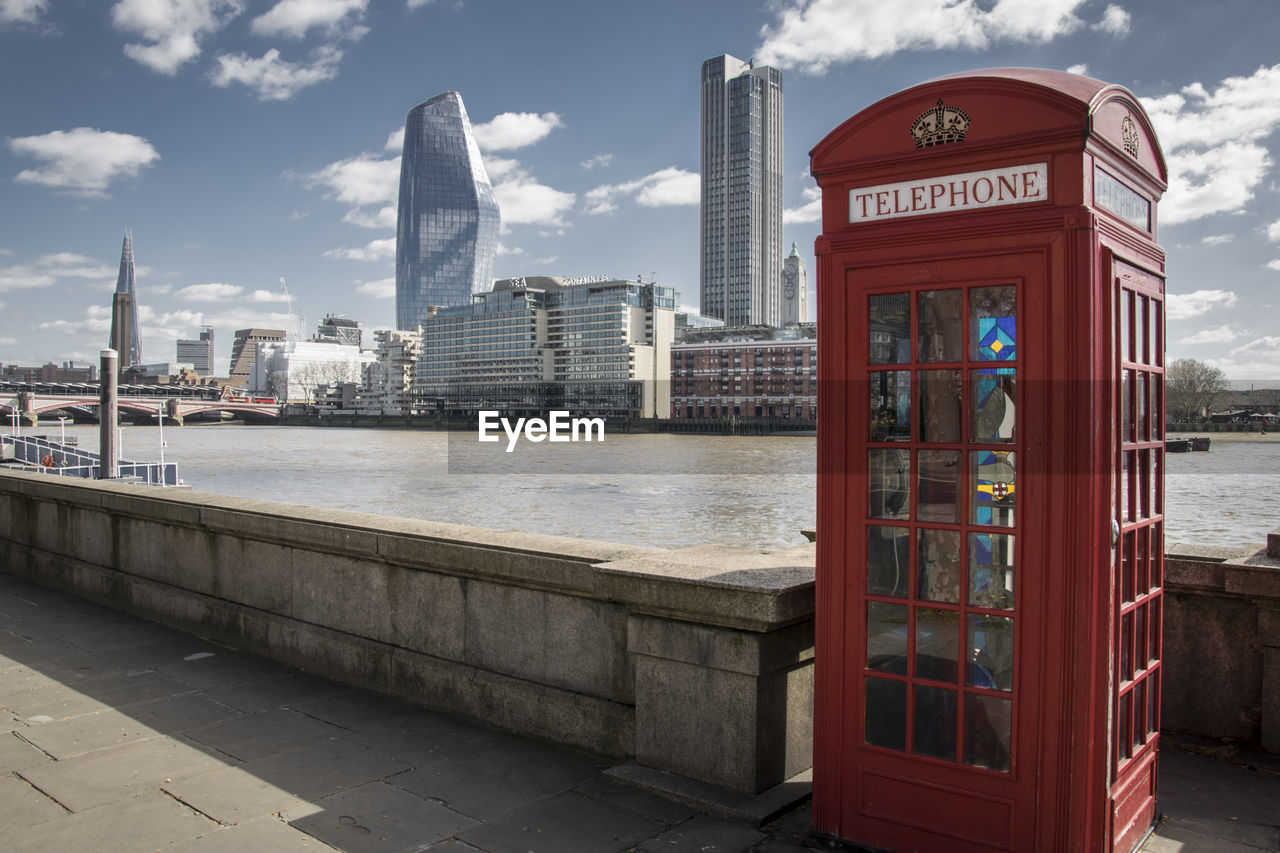 architecture, building exterior, built structure, city, sky, communication, water, cloud - sky, text, nature, telephone, no people, day, connection, western script, telephone booth, building, modern, river, outdoors, office building exterior, skyscraper