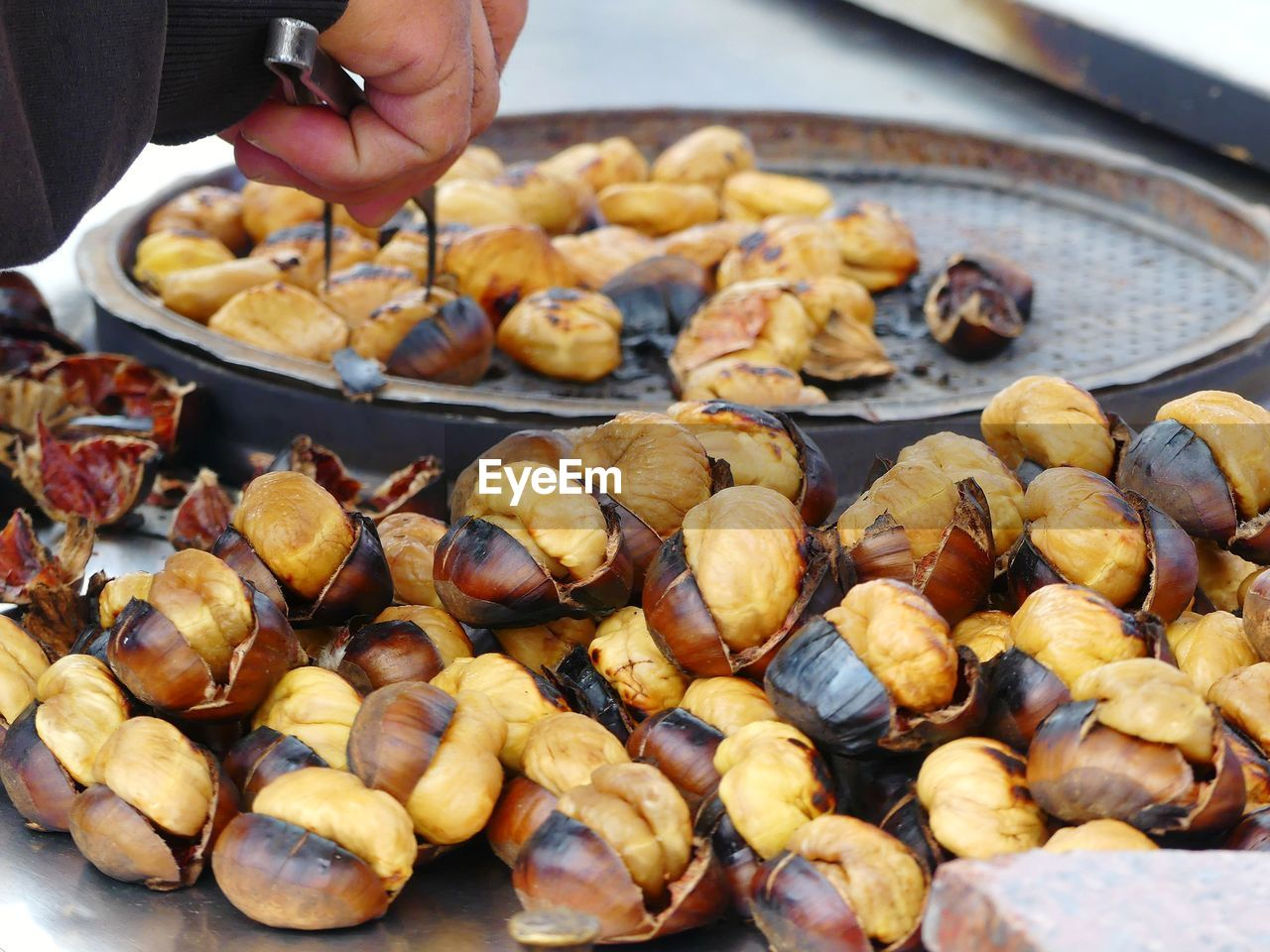 Close-up of man roasting chestnuts