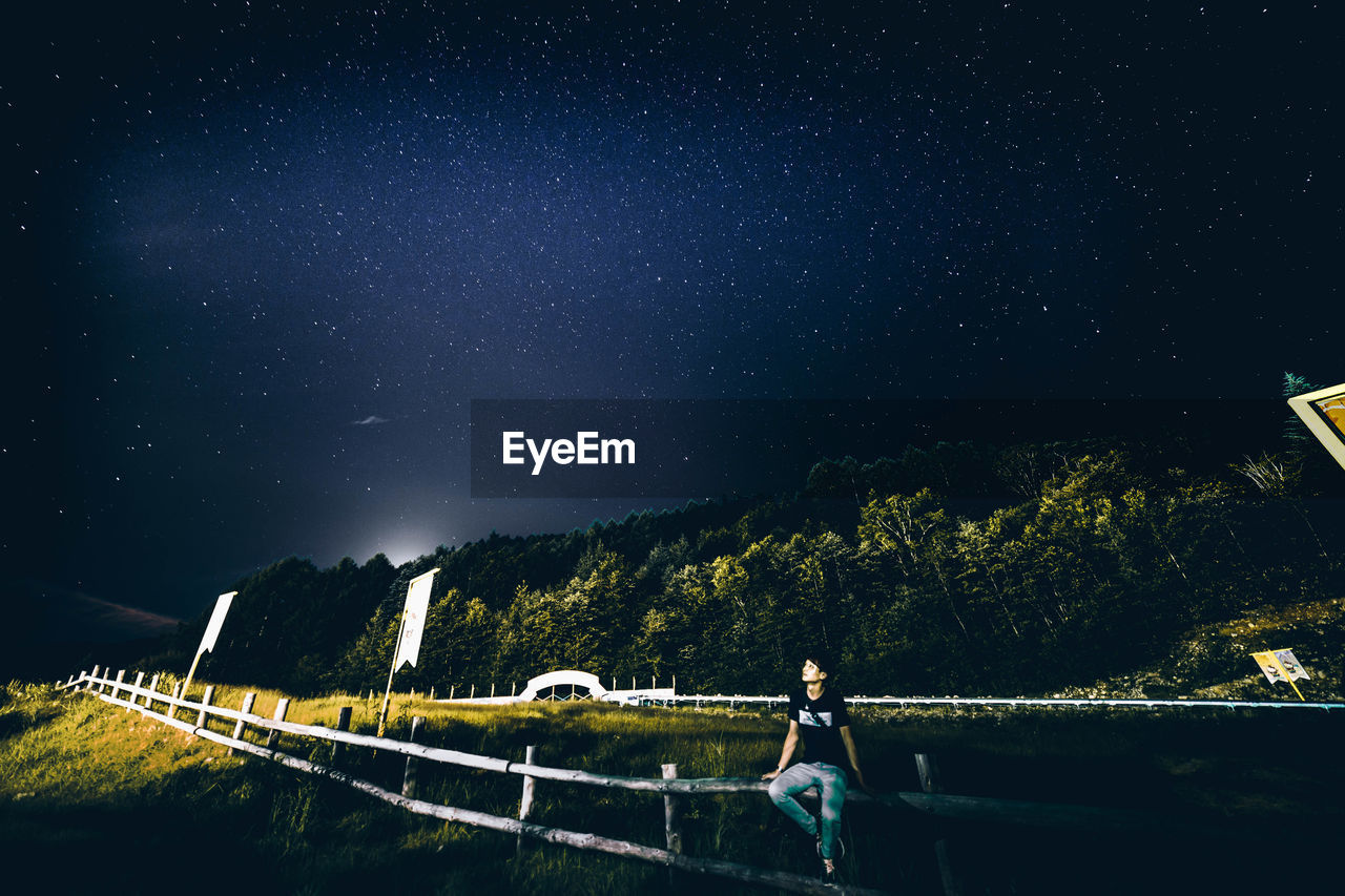 night, space, real people, sky, astronomy, star - space, one person, nature, beauty in nature, star field, standing, star, lifestyles, scenics - nature, leisure activity, railing, galaxy, plant, tranquility, outdoors