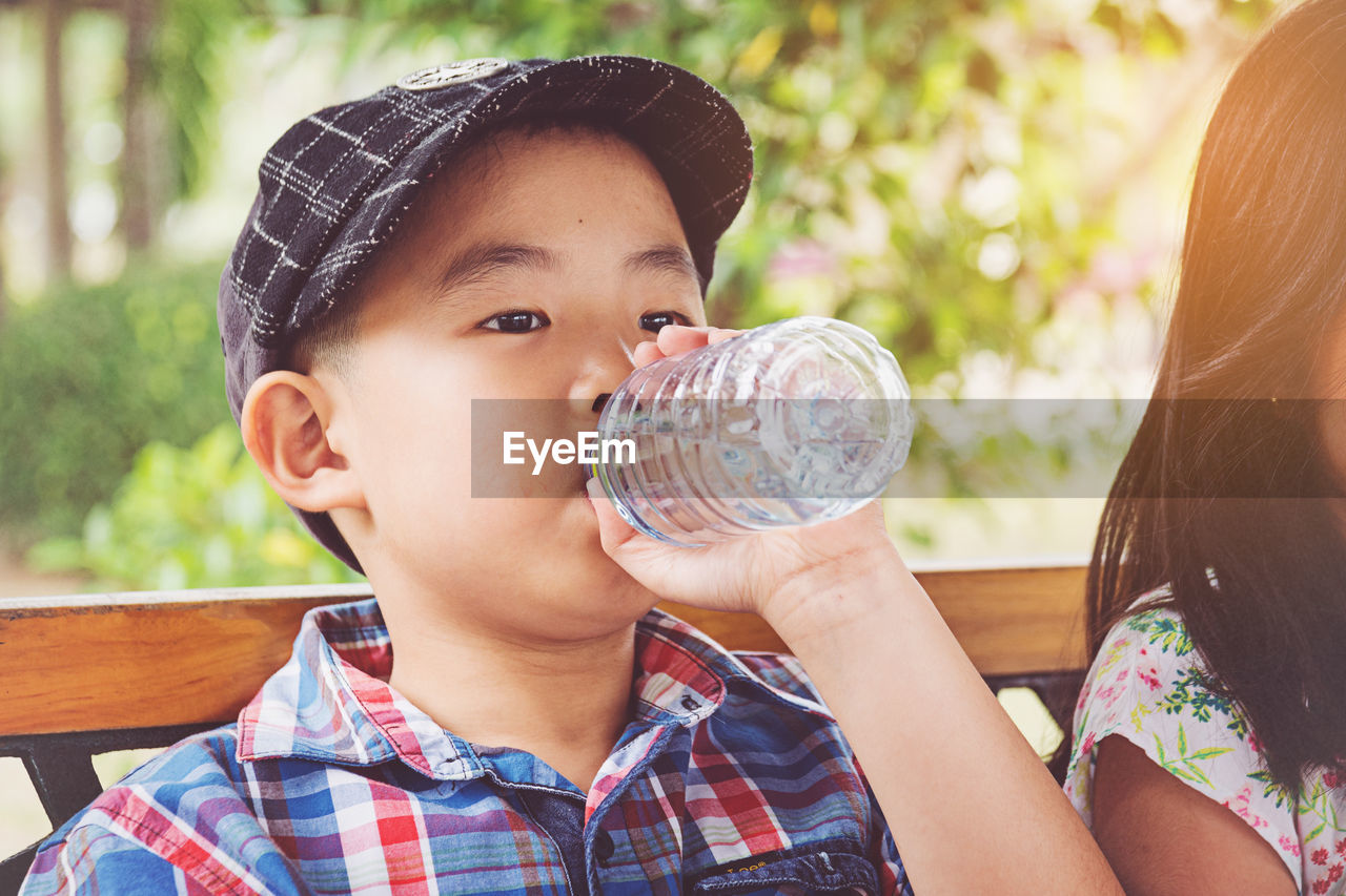 child, real people, childhood, headshot, portrait, boys, men, lifestyles, males, focus on foreground, drinking, holding, leisure activity, drink, day, people, refreshment, casual clothing, outdoors, innocence, glass