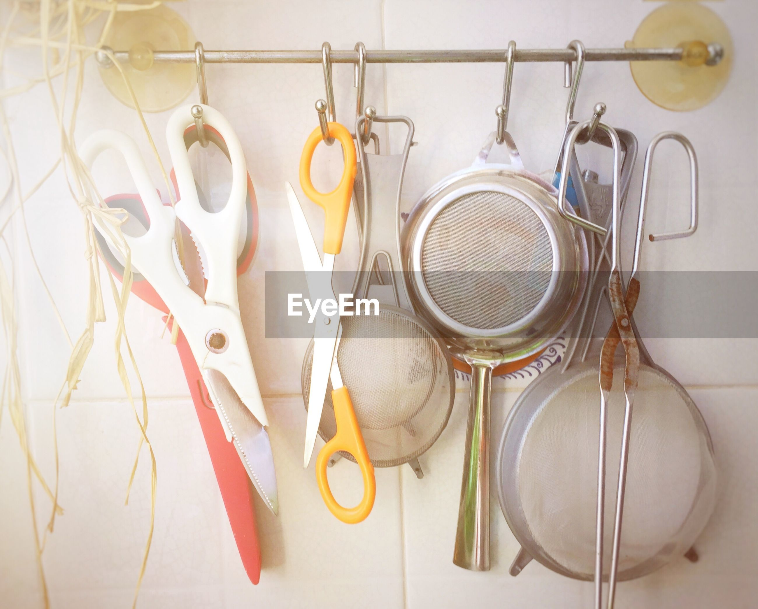Close-up of kitchen utensils hanging against wall at home