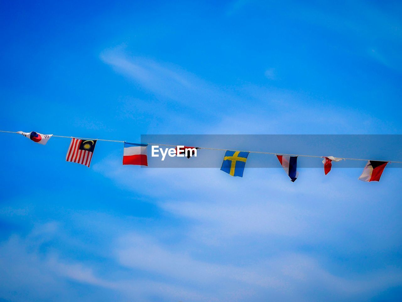 hanging, flag, multi colored, low angle view, sky, day, outdoors, blue, no people, bunting, patriotism