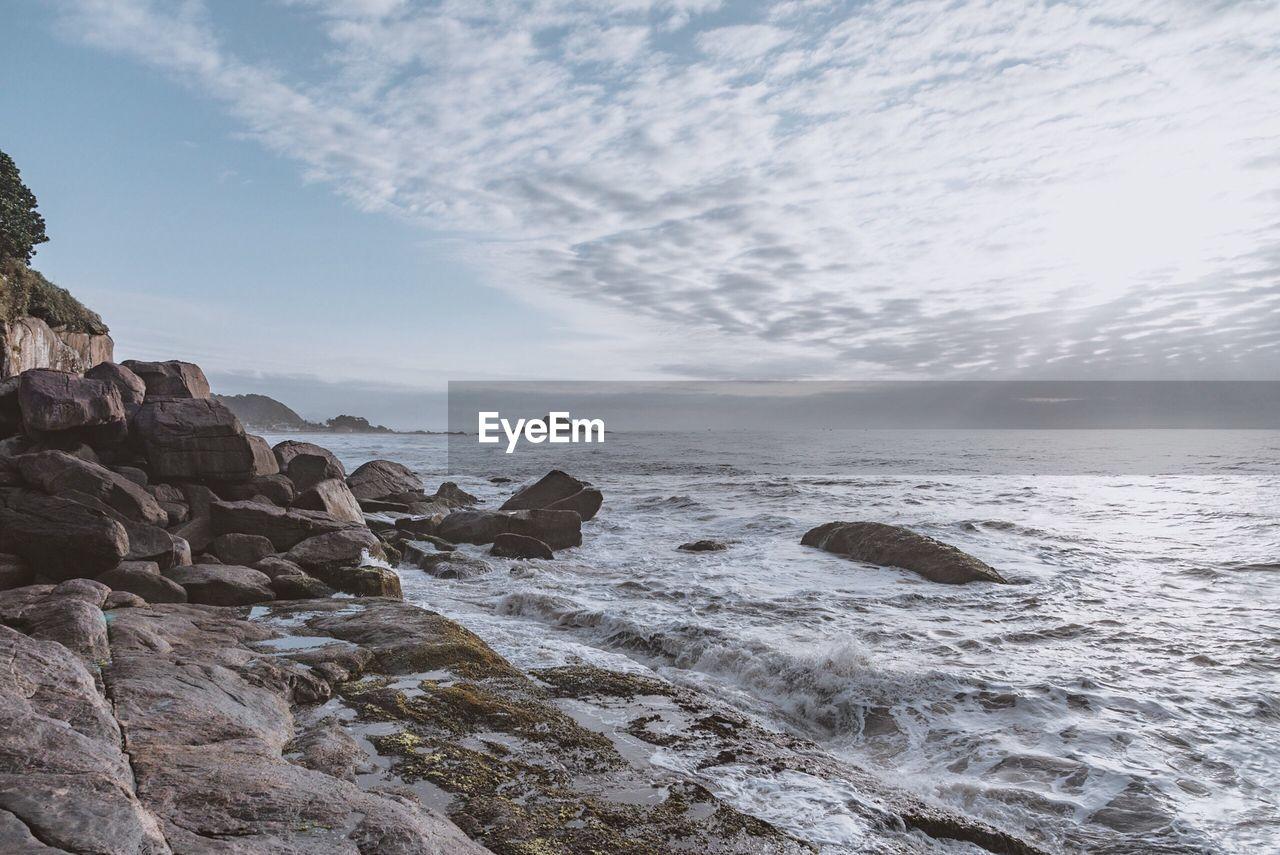 sea, water, beauty in nature, rock, sky, motion, rock - object, scenics - nature, solid, wave, sport, nature, beach, land, no people, aquatic sport, cloud - sky, horizon, non-urban scene, horizon over water, outdoors, power in nature, rocky coastline, breaking