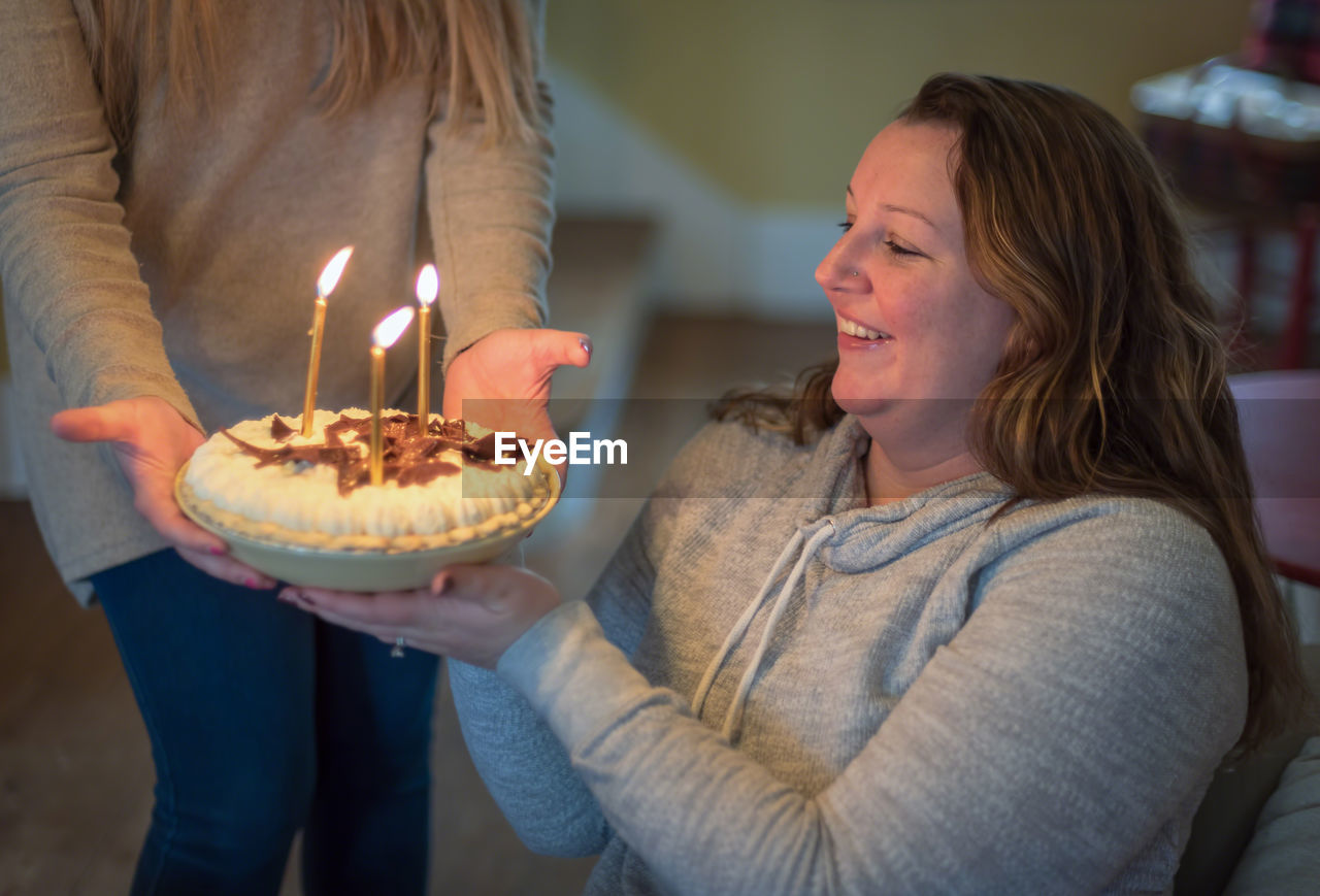 Midsection of woman giving lit birthday cake to friend at home