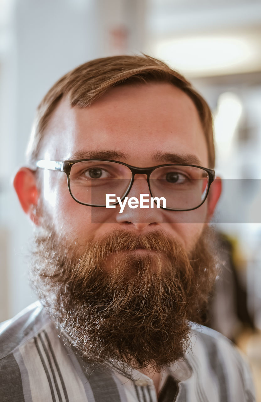 portrait, eyeglasses, facial hair, beard, headshot, glasses, looking at camera, one person, front view, close-up, focus on foreground, indoors, real people, men, adult, males, mid adult, young adult, mustache, hairstyle, human face, making a face
