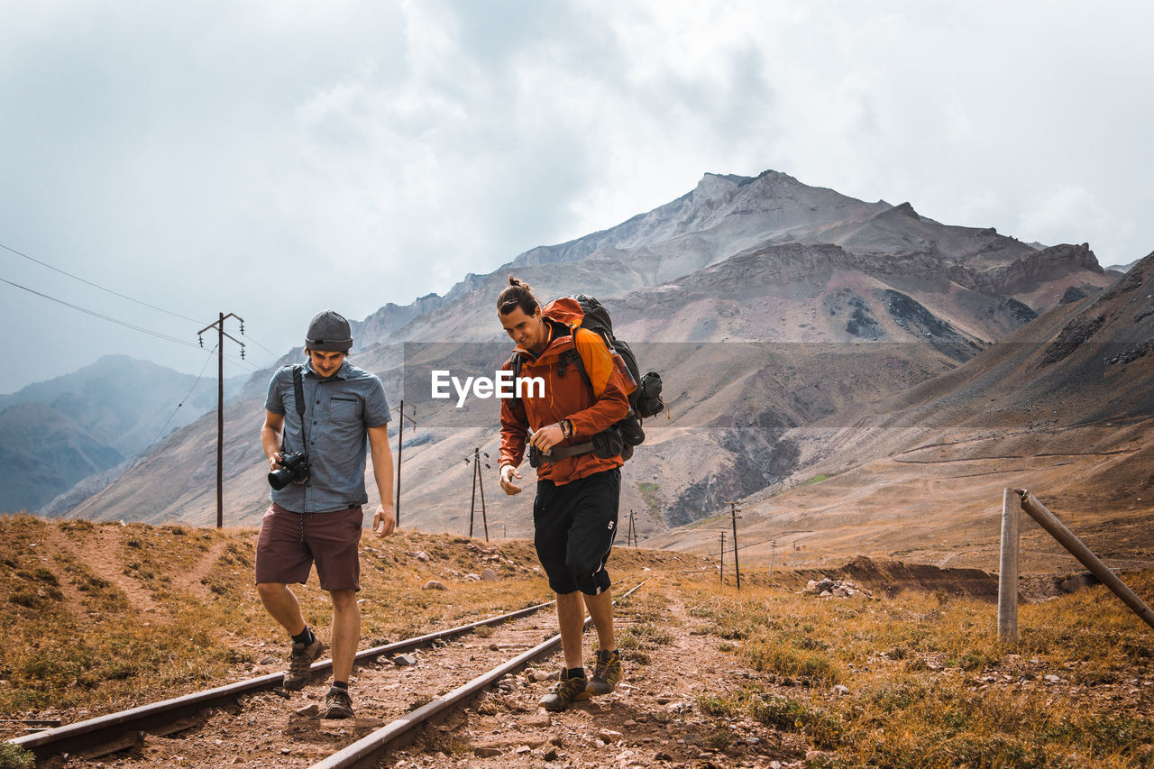 Young Friends Walking On Railroad Tracks Against Mountains