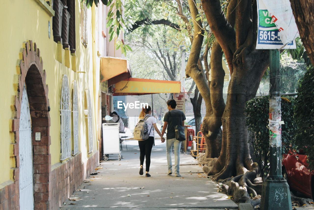 REAR VIEW OF PEOPLE WALKING ON STREET ALONG TREES