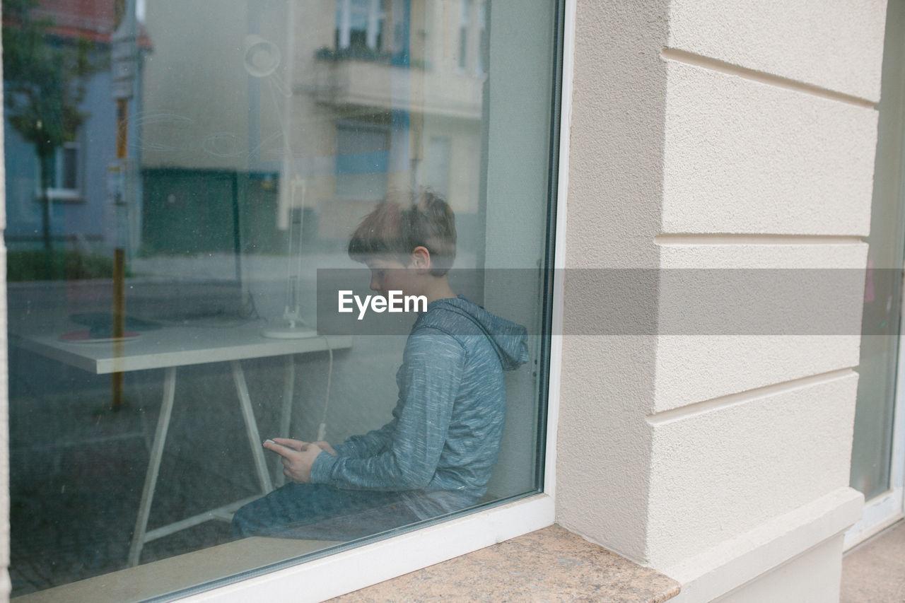 MAN LOOKING THROUGH WINDOW IN BUILDING