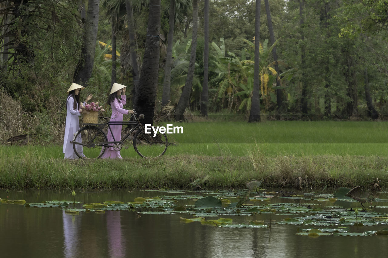 Female friends walking with bicycle by lake on land