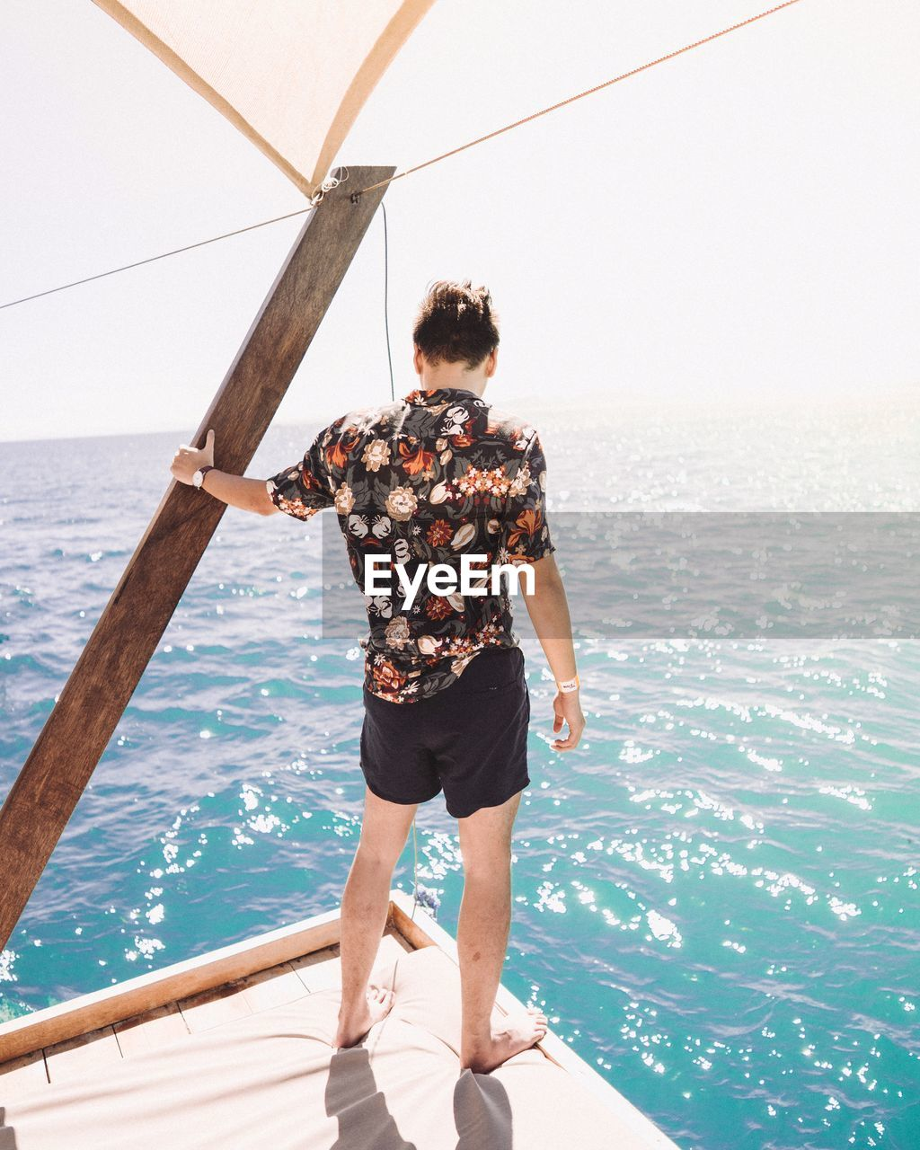 Rear View Of Man Standing On Pier While Looking At Sea Against Sky