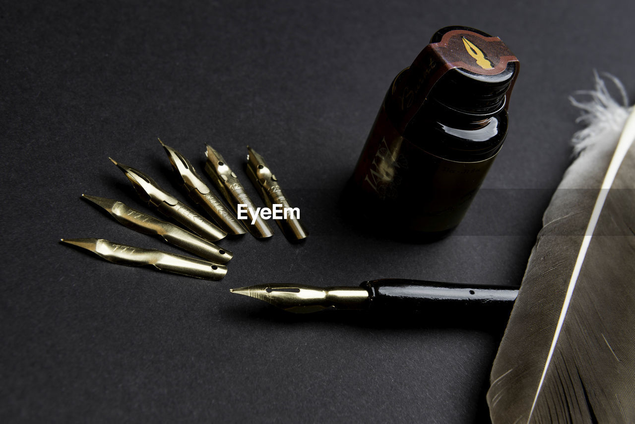 still life, table, high angle view, pen, indoors, no people, metal, close-up, bullet, black background, ink well, day