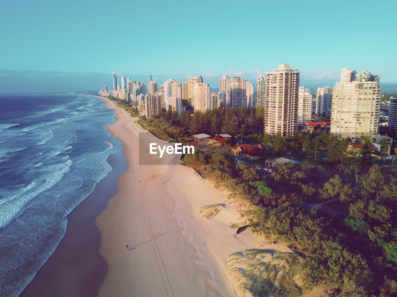 sea, architecture, beach, water, built structure, sky, building exterior, city, land, nature, plant, day, building, clear sky, tree, sand, outdoors, cityscape, no people, office building exterior, skyscraper