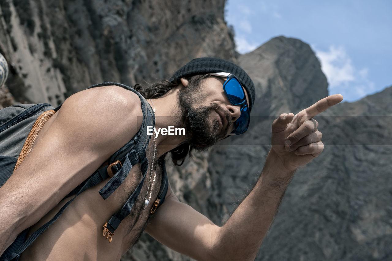 Shirtless man pointing against mountain