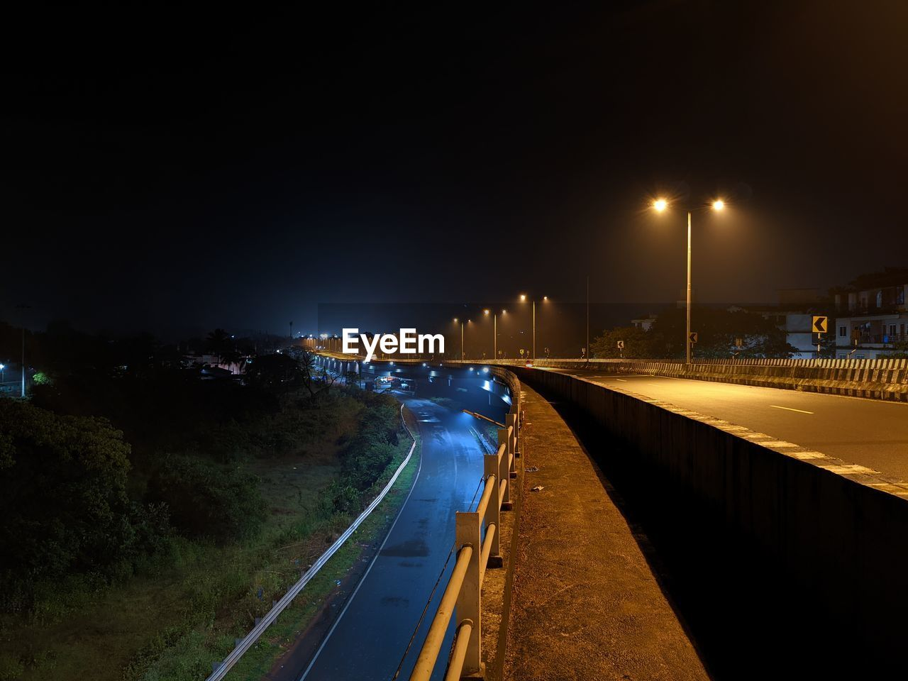 VEHICLES ON ROAD AGAINST SKY AT NIGHT