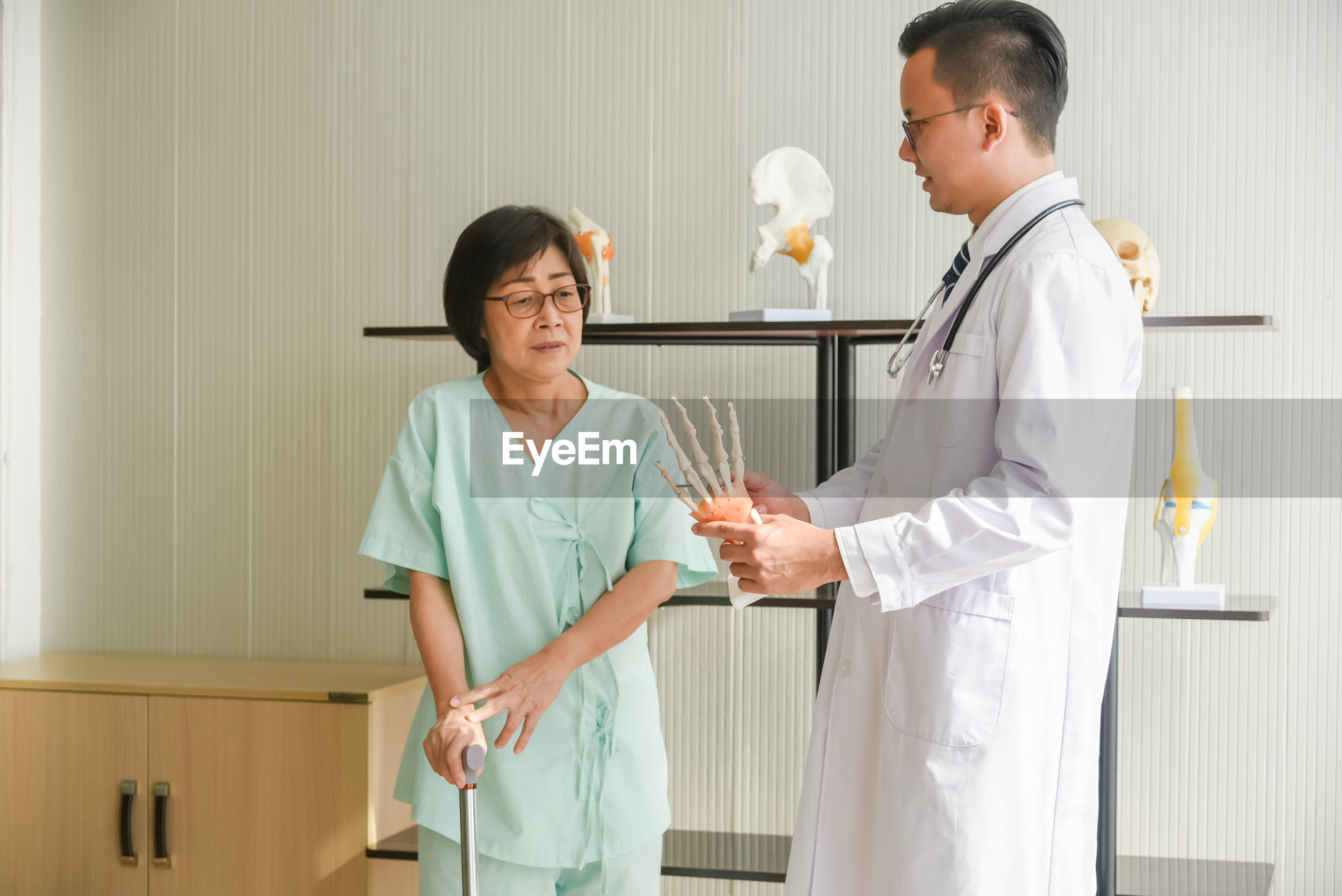 Doctor explaining hand figurine to female patient suffering from pain