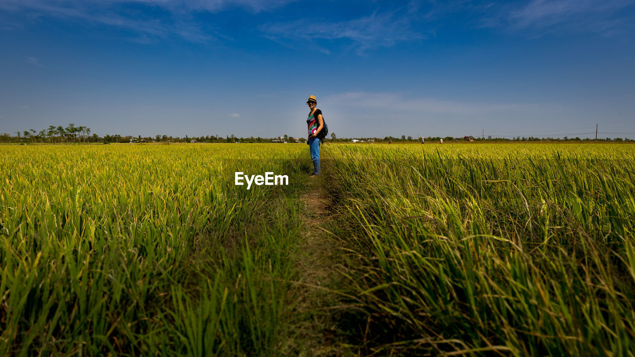 Full Length Of Woman Standing Amidst Crops Growing On Field
