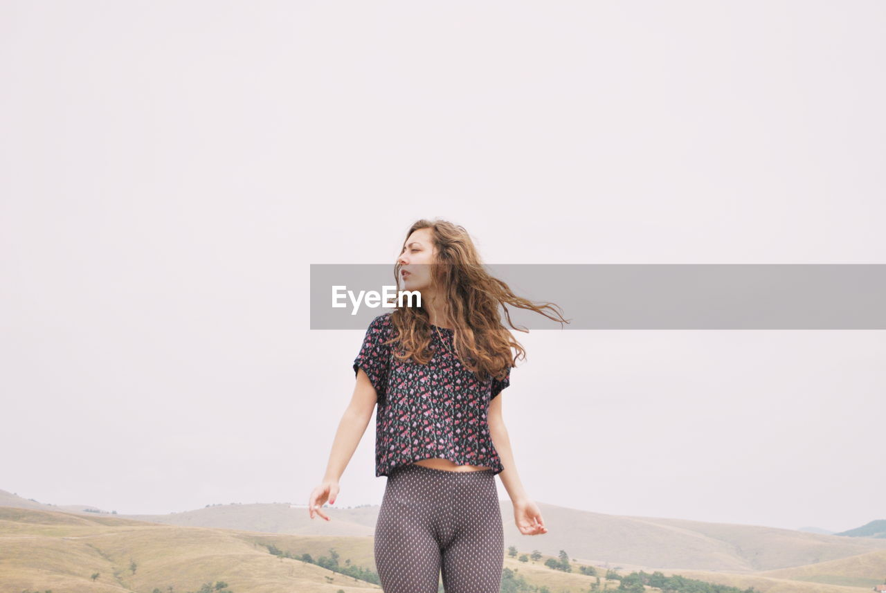 Young Woman With Tousled Hair Standing Against Clear Sky