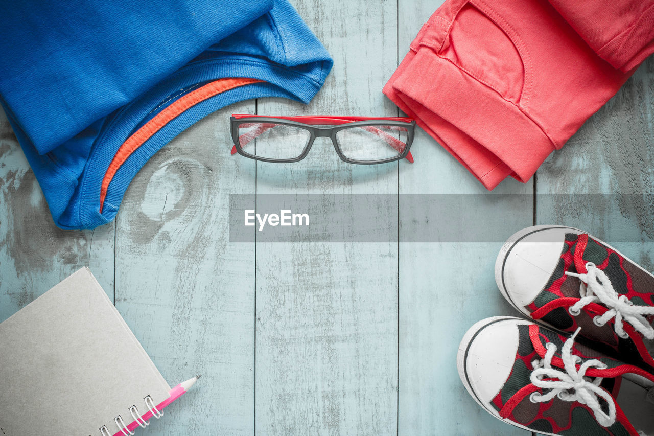 shoe, glasses, indoors, high angle view, one person, casual clothing, clothing, human body part, directly above, fashion, adult, eyeglasses, preparation, pair, red, jeans, blue, group of objects, paper, personal accessory