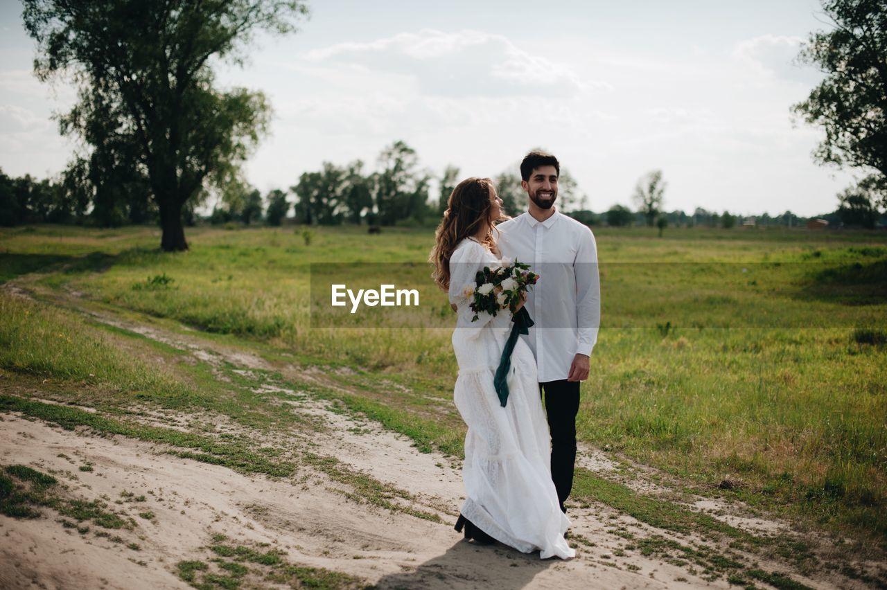 Bride And Bridegroom Standing On Field