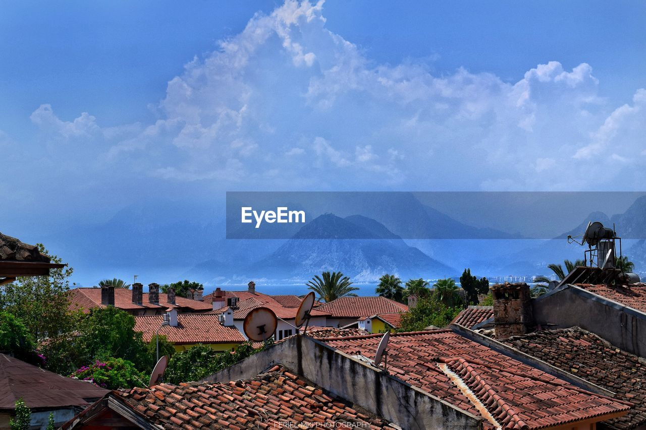 roof, architecture, built structure, building exterior, sky, cloud - sky, building, mountain, house, residential district, roof tile, nature, city, day, town, high angle view, tree, no people, mountain range, outdoors, townscape