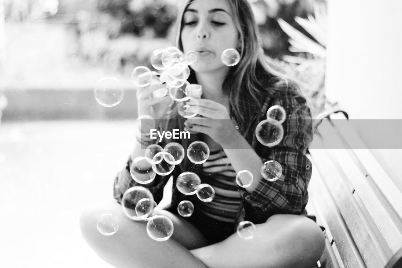 Young woman blowing soap bubbles while sitting on bench