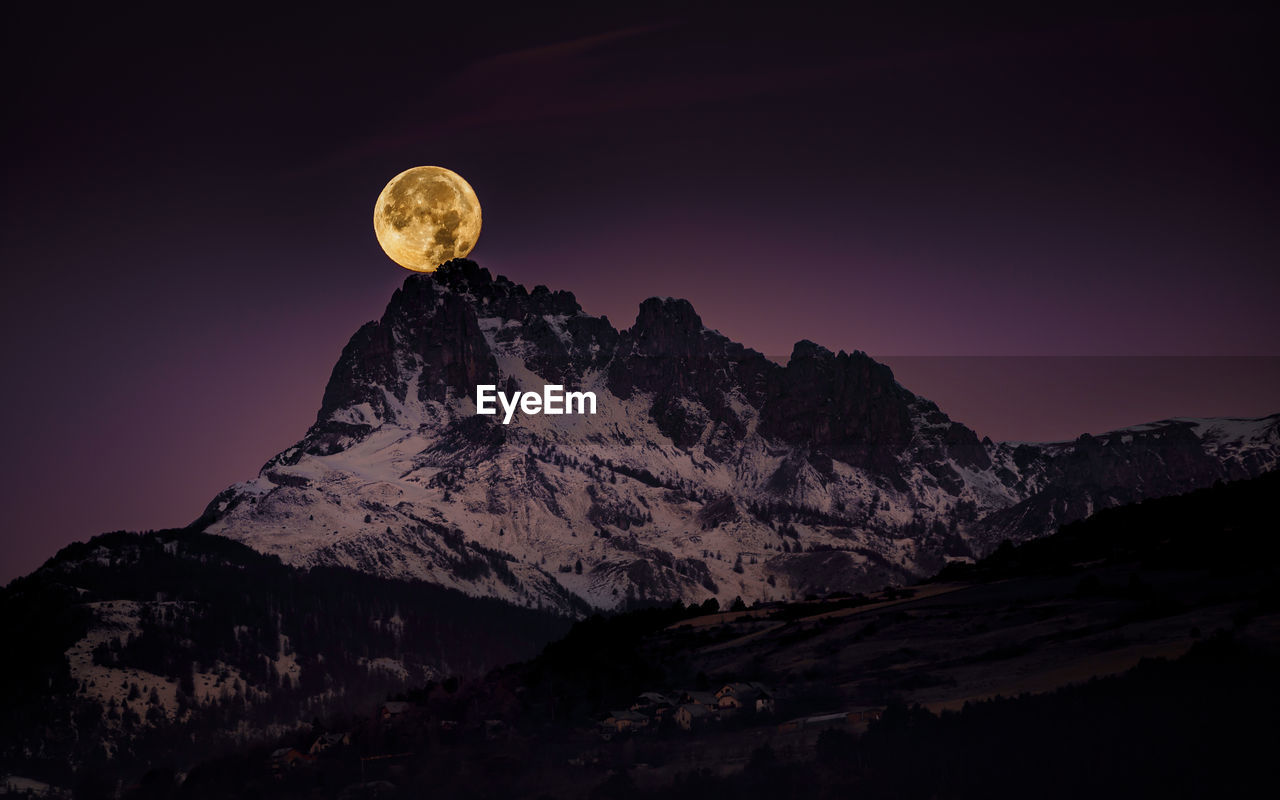 Scenic view of snowcapped mountains against sky at night and the big red full moon