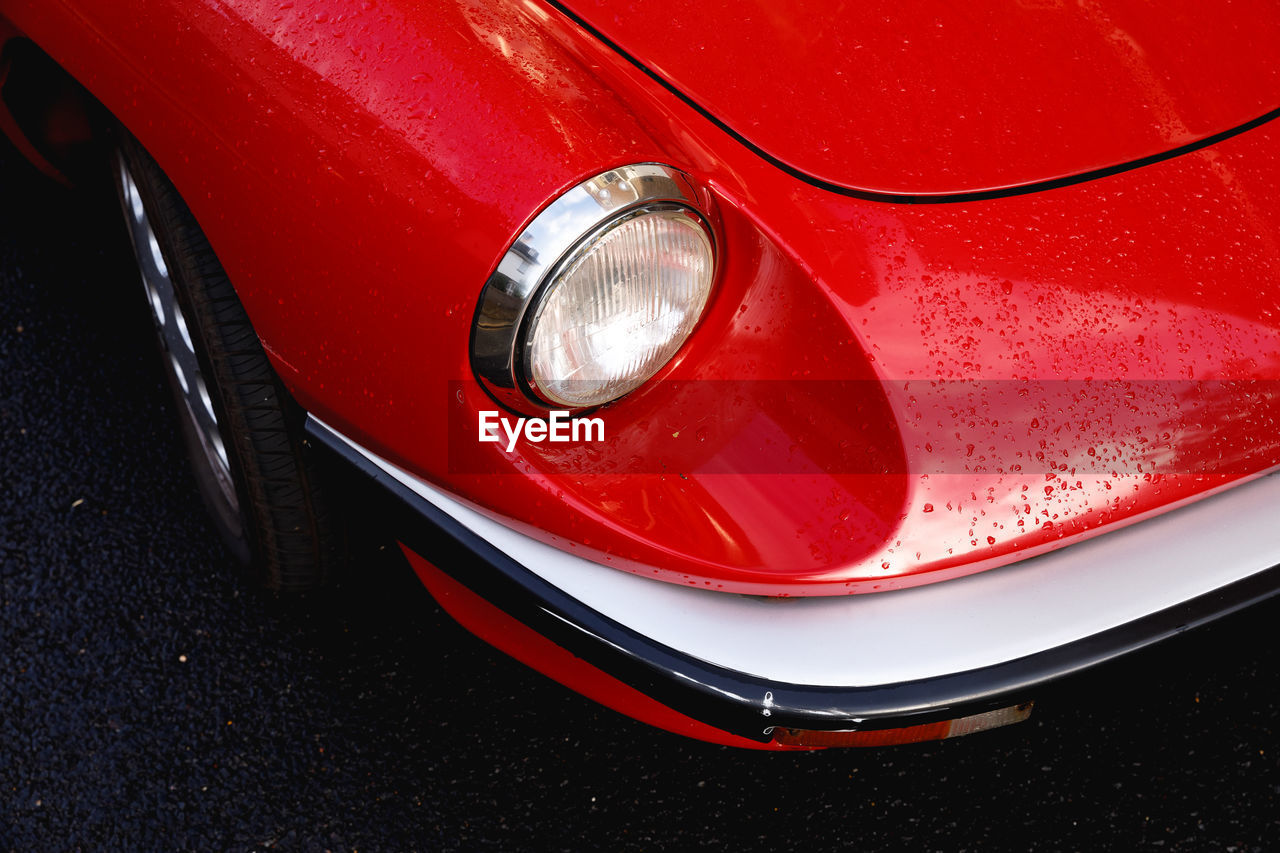 transportation, mode of transportation, land vehicle, car, red, motor vehicle, close-up, headlight, retro styled, high angle view, vintage car, no people, day, stationary, shiny, metal, outdoors, reflection, vibrant color, wheel, chrome, silver colored