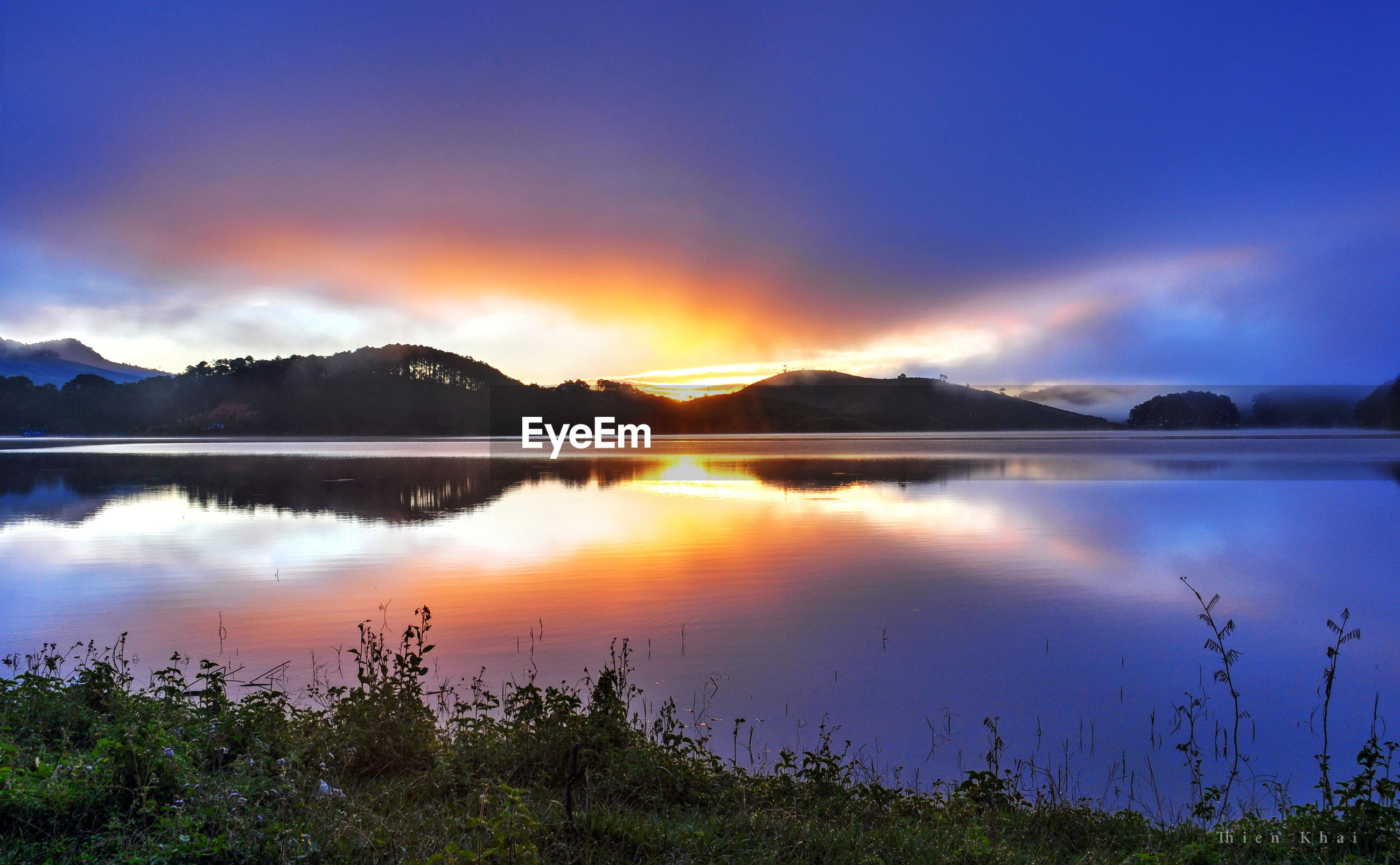 SCENIC VIEW OF LAKE BY SILHOUETTE MOUNTAINS AGAINST SKY AT SUNSET