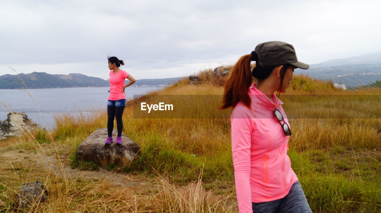 REAR VIEW OF WOMAN STANDING ON FIELD